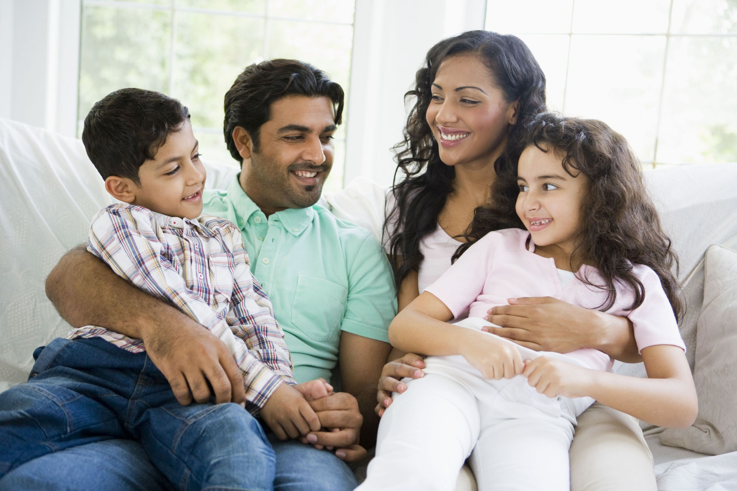 A smiling South Asian father and mother sitting on a couch with the son and daughter in their laps.