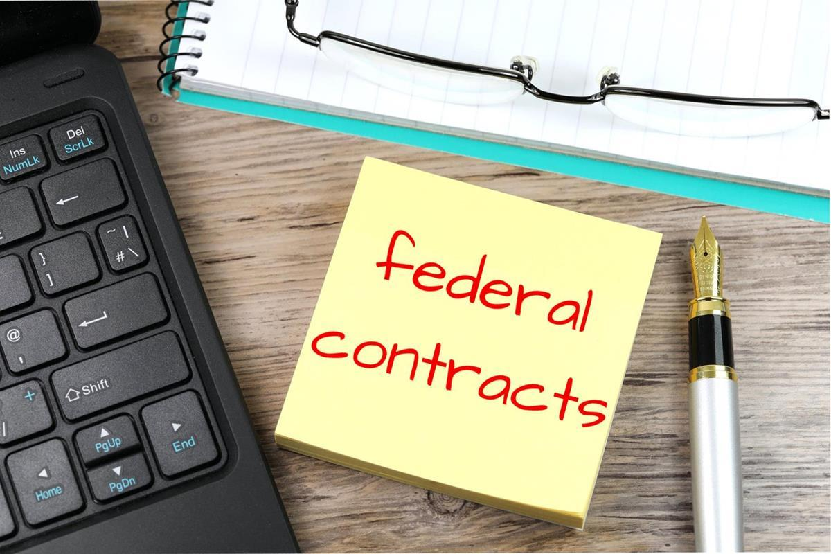 """The phrase """"federal contracts"""" written on a sticky note next to a laptop"""