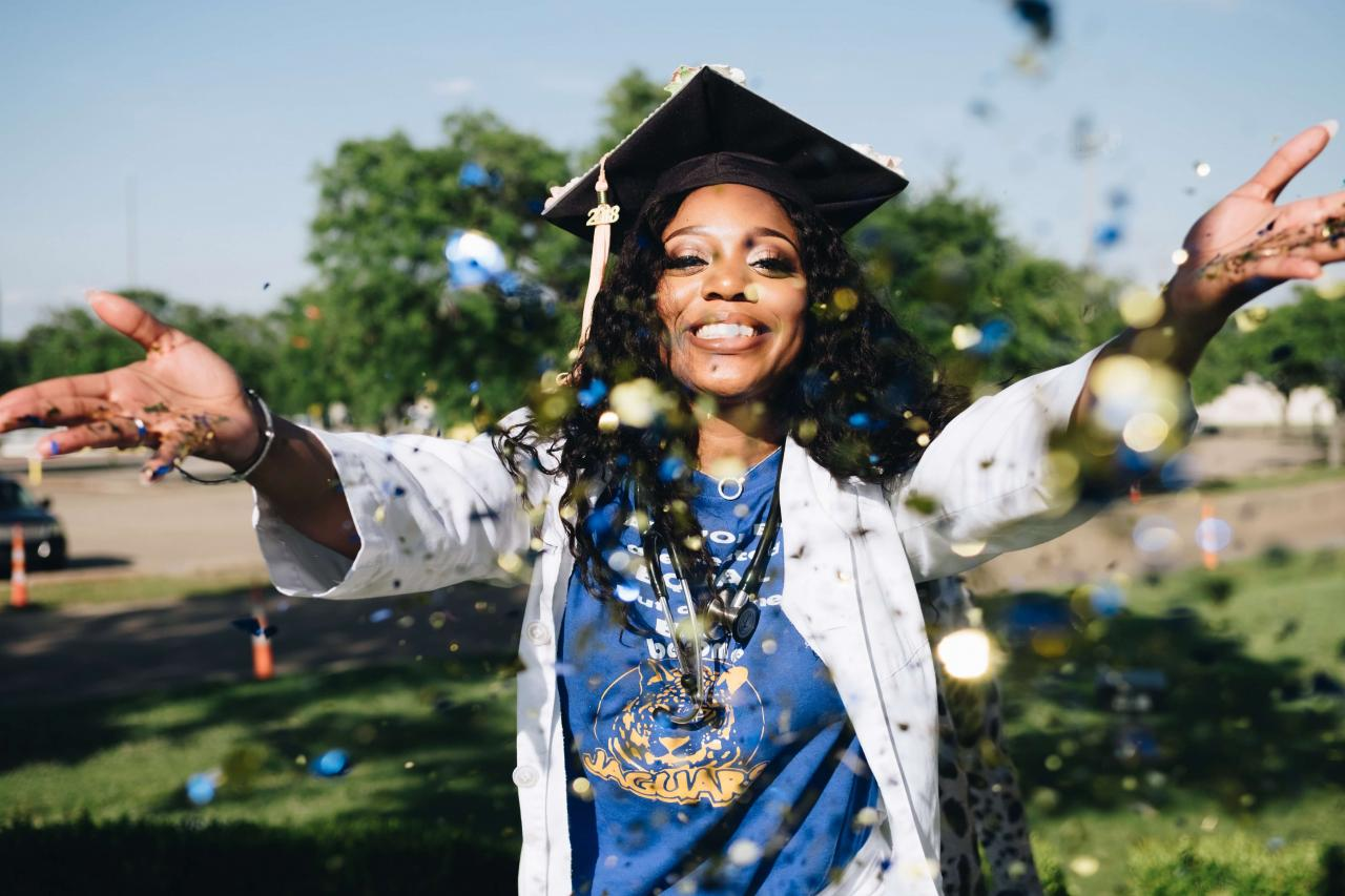 Young woman in a cap and gown celebrating graduation.