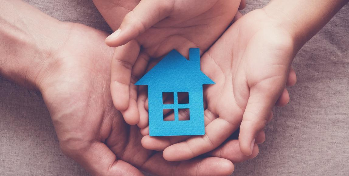 Hands holding paper cutout of a house