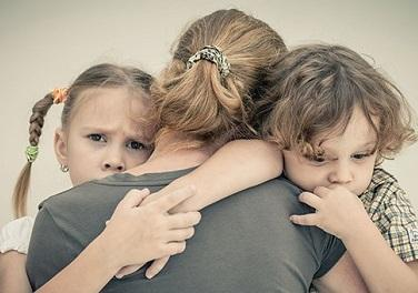 Photo of mother hugging daughter and son